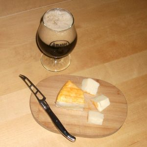 Amager Bryghus / Stillwater Darkest of Suns with a red rind soft cheese.