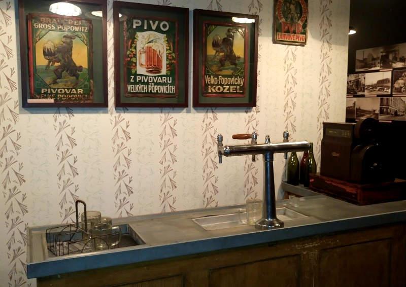 Rundvisningen på Kozel er fyldt med gamle plakater og billeder. Her over baren i en gammel ølstue