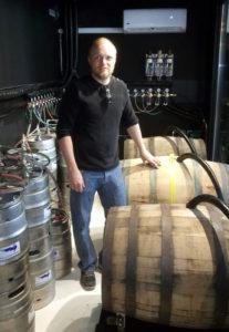 Brygger Torben Stenholdt i ølrummet med de tre tønder fadlagret øl.